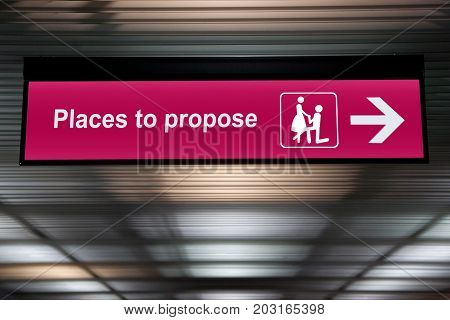 pink place to propose sign hanging from ceiling , proposal marriage concept