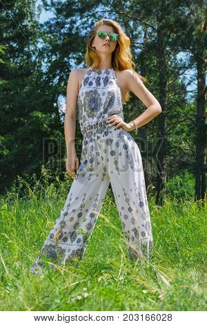 Beautiful romantic girl in a clearing in the forest. Modern hippie style. Beauty, fashion outdoor.