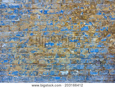 A brick-built aged brick wall. A blue old brick wall.