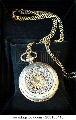 Metal elegant antique pocket Czech timepiece on black velvet background. Indoors close-up vertical image.