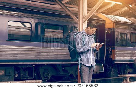 Asian Man Backpack For Travel At Train Station And Using Tablet Searching Map Location.