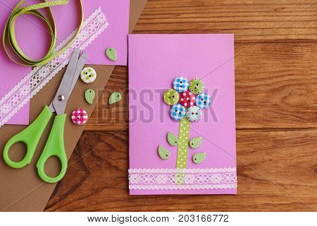 Greeting card with a flower from wooden buttons, decorated with lace. Birthday card for mom, Mother's day diy. Tools and materials on a wooden table. Greeting card kids can make. Top view