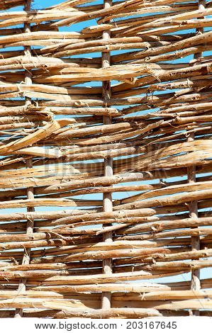 Rattan wattled wicker pattern. Twigged textured fence. Outdoors close-up.