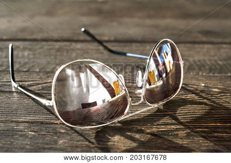 Metal thin trendy sunglasses on wooden table. Evening light. Outdoors closeup.