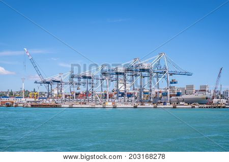 Auckland port with shipping containers cranes and ship providing transportation for imports and exports in New Zealand NZ
