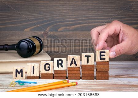 Migrate concept. Wooden letters on the office desk, informative and communication background.