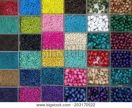Background of colorful bright beads in boxes set for needlework