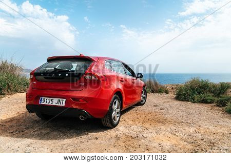 Santa Ponsa Mallorca Spain - May 28 2015: Red car Volvo v40 stands on the edge of a cliff in front of the Mediterranean sea. Morro d'en Pere Joan bay Es Malgrat rocks in Santa Ponsa Mallorca Spain.