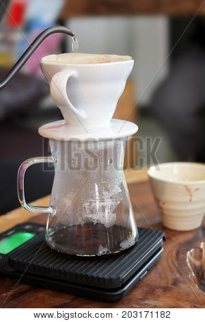 Hand Drip Coffee, Drip Coffee Glass Kits and  roasted, grinded coffee beans contained in a paper filter with hot water.