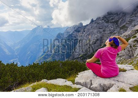 Active woman exercising in the nature above the beautiful valley. Yoga and meditation in the mountains with view. Active lifestyle - healthy lifestyle.