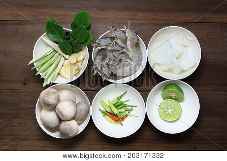 Ingredient of tom yum ( Lemongrass, Galangal, kaffir lime leaf,shrimp, onion, Paddy straw mushroom ,chili and lime) in white bowl on wooden background, thai food, prepare food, uncooking.