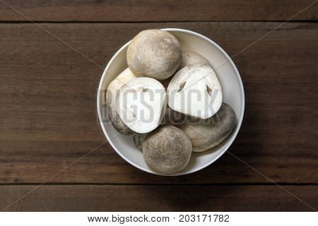 Cut through Paddy straw mushroom in a white bowl on wooden background, edible mushroom, food ingredient,  Asian cuisines.