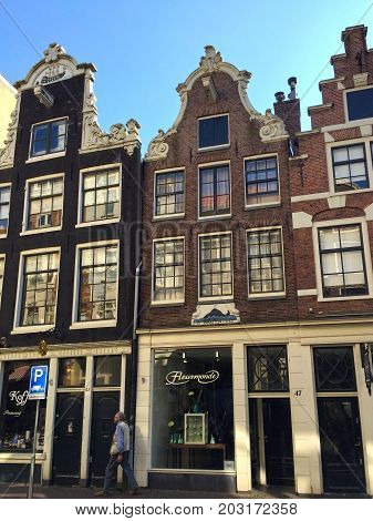 AMSTERDAM, NETHERLANDS - MAY 8, 2016: A typical Amsterdam street with old dutch buildings in Old Town of Amsterdam, Netherlands.