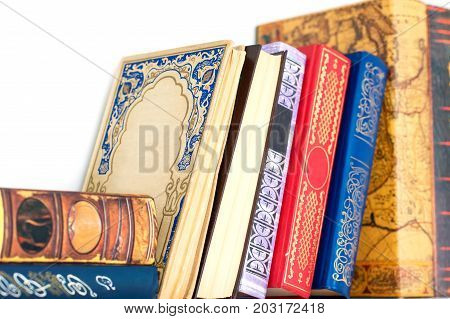 Collection of many different old ornamental hardcover books on white shelf. Indoors multicolored horizontal image.
