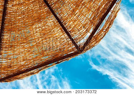 Wattled straw beach umbrella on blue cloudy sky background. Outdoors summertime multi colored closeup horizontal image. View from below.