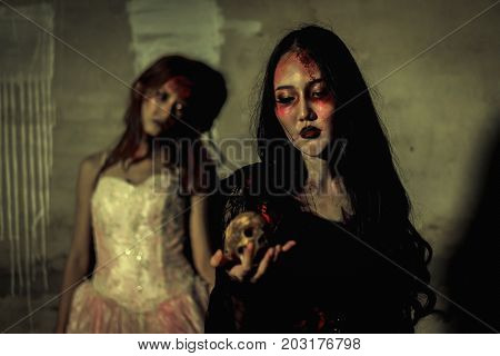 Witch death the ghost holding skull and zombie in dress women with blood skin is screaming darkness and nightmare background horror of scary fear on hell is monster devil girl in halloween festival concept