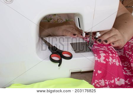 woman seamstress sitting and sews on sewing machine. Dressmaker work on the sewing machine. Hobby sewing as a small business concept. designer making a garment in her workplace