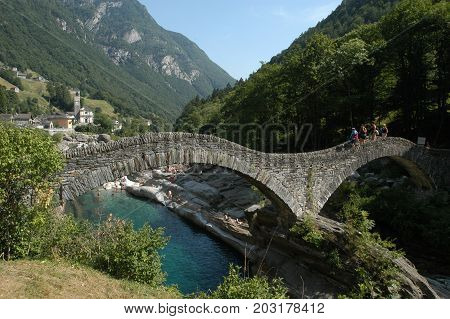 Lavertezzo, Switzerland: 1 September 2014: Tourists visiting the famous roman bridge of Lavertezzo on Verzasca valley on the italian part of Switzerland