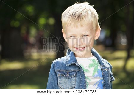 Portrait of a young boy in a jeans jacket in the background of a summer park