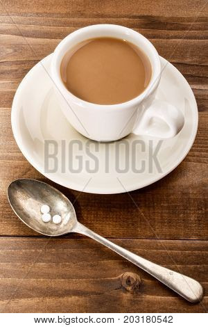 cup of warm coffee with milk and sweetener on a spoon