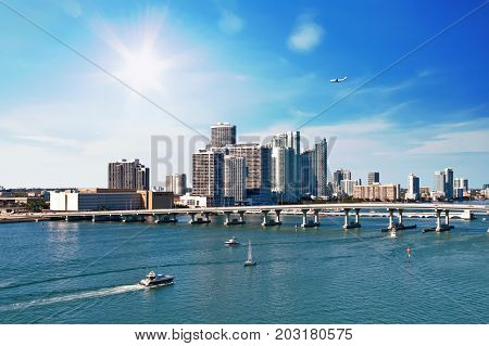 Miami's Biscayne Bay with a commercial jet overhead and boats sailing under bridge