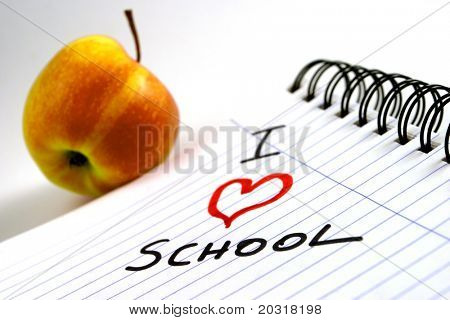 """paper-block with """"i love school"""" written on it,apple in the background"""