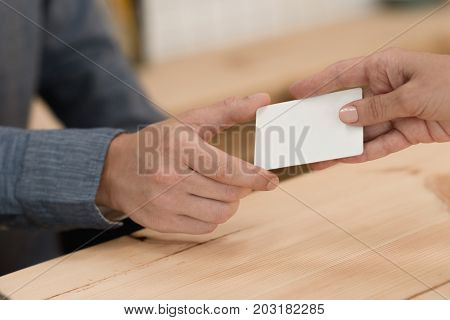 partial view of woman giving credit card to waiter for payment in cafe