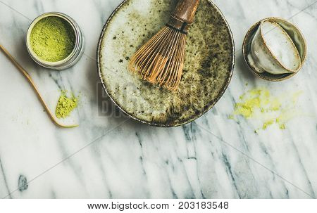 Flat-lay of Japanese tools and bowls for brewing matcha green tea. Matcha powder in tin can, Chashaku spoon, Chasen bamboo whisk, Chawan bowl, cups, grey marble background, top view, copy space