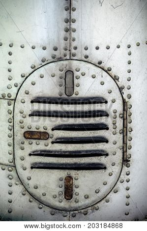 Aluminum surface of the aircraft fuselage. Rivets and hatches. Weather, scratched and corrosive surface.