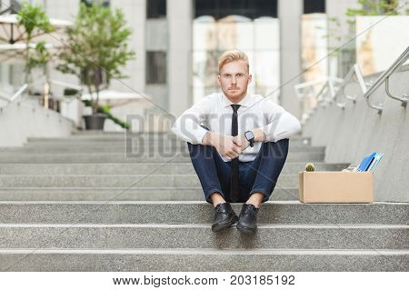 Unfair Ginger Worker Sit On Stair And Seriosly Looking At Camera.