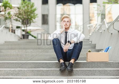 Unfair Ginger Young Adult Worker Sit On Stairs And Wondering.