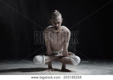 Young caucasian man yoga instructor doing Cock Pose Rooster Posture Kukkutasana asana exercise from yoga on black background with powder all around