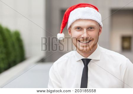 Portrait Of Success Ginger Businessman On Santa Hat. Looking At Camera And Toothy Smile.
