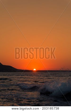 View on a breathtaking warm Sunset on the Horizon. Close-up of crashing Waves in front of a beautiful Sunset. Travel and Beach Backgrounds.