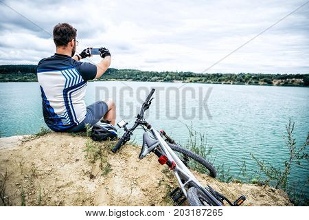 man sitting alone on the peak of the hill with bicyle and taking picture of the view