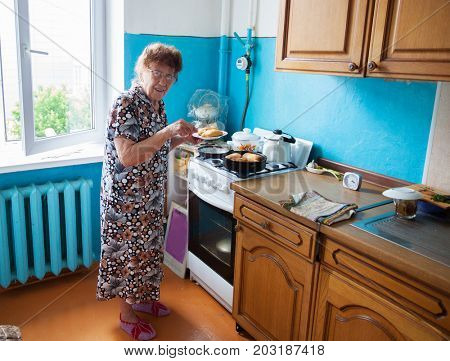 Old woman at home. Elderly woman on the kitchen.