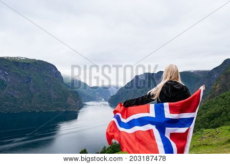 Panorama of Aurlandsfjord. Tourist girl with the flag of Norway enjoys a beautiful view of the fjord and mountains