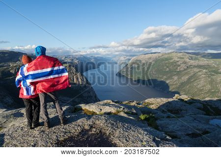 Pathway Pulpit Rock. Couple with the flag of Norway looks at the panorama of the Lysefjord. Tourist attraction. Sunny weather in the mountains