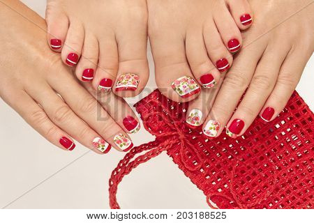 Red French manicure and pedicure with design of roses on a white background.