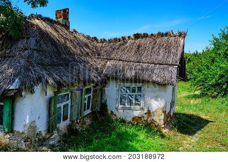 Close up weathered rustic hut with thatched roof in village