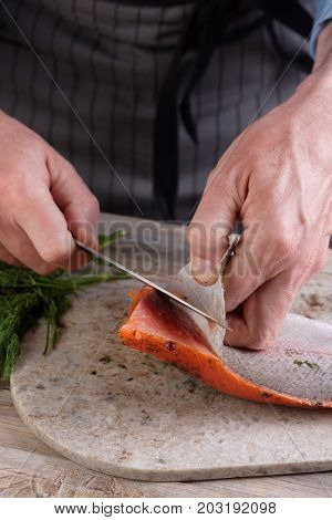 Cook removing skin from salted salmon fillet on a cutting board