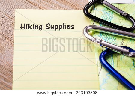 Hiking Supplies list concept on notebook and wooden board with carabiners