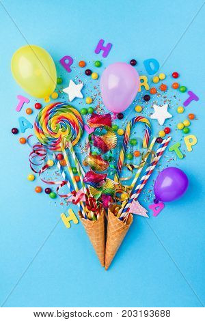 Tasty appetizing Party Accessories Happy Birthday Sweets Treat Balloon Candy Lollypop Colorful Bouquet Bright Blue Background Top View Fashion Conceptual Holiday Flat Lay