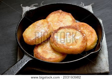 Curd cheese pancakes in cast iron pan close up view