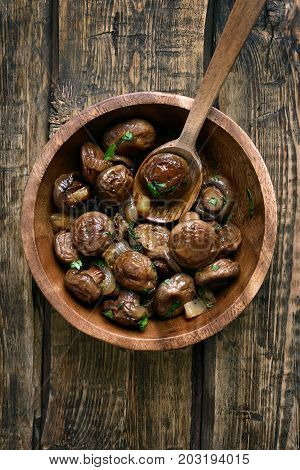 Cooked fried mushrooms with onion in bowl on wooden background top view