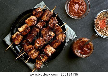 Barbecued pork kebabs and tomato sauce on dark stone background top view