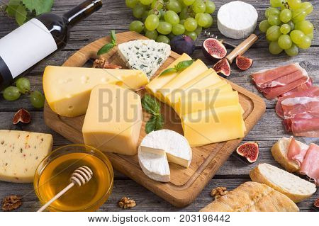 Different kind of cheese with wine figs walnuts jamon