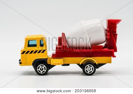Yellow cement mixer truck toy isolated on white background. Building and construction industry industrial business commercial concept.