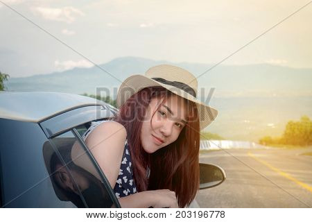 Relaxed happy traveler Young beatiful asian gilr lean out of the car and smiling with mountain road background.