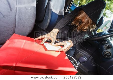 Anti theft system problem concept. Burglar thief man wearing black clothes breaking into car stealing smartphone and red shopping bag